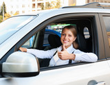 woman sitting in car and showing thumbs up