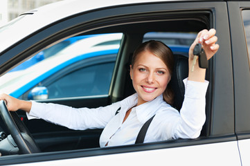 woman sitting in car and showing the car keys