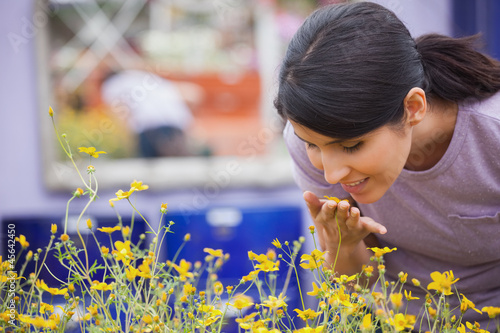 Woman smelling yellow flowers happily