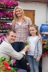 Mother and daughter receiving flower pot from employee