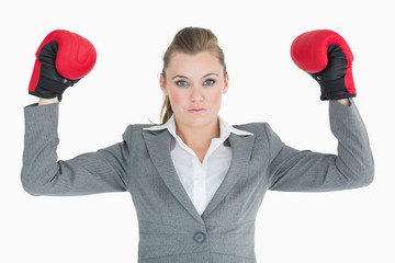 Businesswoman raising her hands with boxing gloves