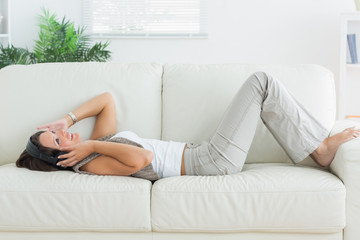 Woman lying on the sofa and listening music