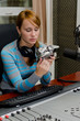 Female dj sitting in front of a microphone on the radio