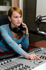 Portrait of female dj working in front of a microphone