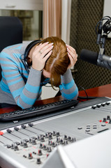 Depressed female dj working in front of a microphone