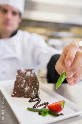 Chef applying finishing touch to desert