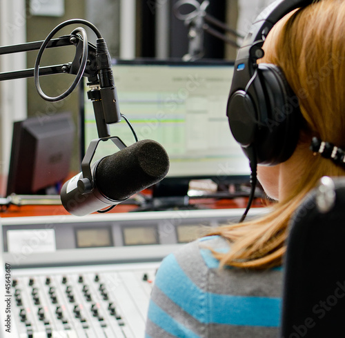 Rear view of female dj working in front of a microphone