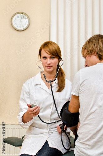 Young female doctor measuring patient's blood pressure