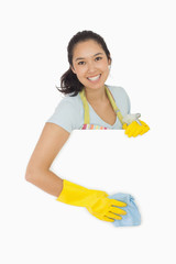 Smiling woman wiping down white surface