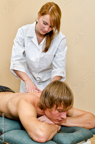 Young handsome man getting back massage lying on massage table