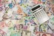 Banknoten aus diversen Ländern der Welt mit einem Taschenrechner