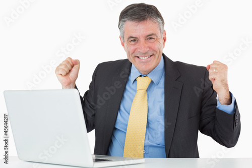 Succesful man sitting at his desk with laptop