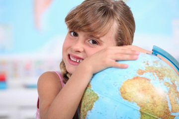 Young girl hugging a globe