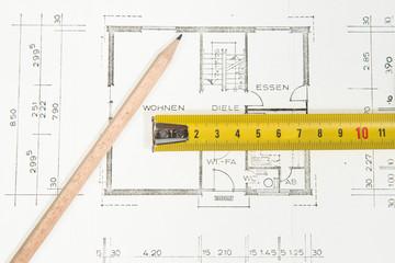 Bauplan Eigenheim mit Bleistift und Metermaß