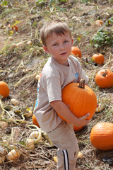 Little boy holding big pumpkin at a farm