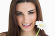 Brunette holding a flower and smiling