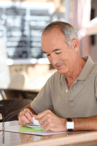 Grey-haired man sat in cafe drinking espresso