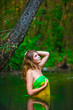 Blonde nude young woman standing waist water in the river in gre