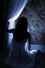Young girl standing by the window, watching the stars