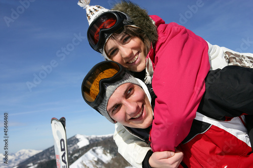 Young couple messing around on the ski slopes