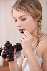 Woman eating bunch of grapes