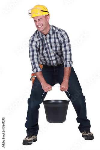 craftsman carrying a very heavy bucket