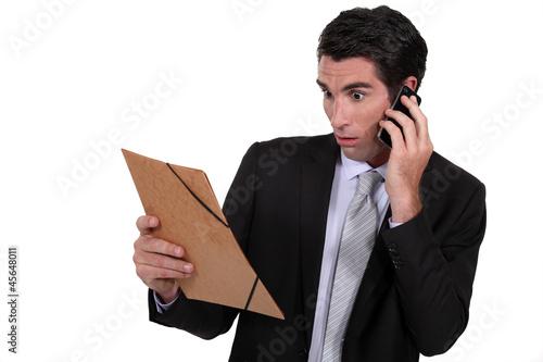 Shocked man looking at a file folder