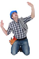 Kneeling laborer looking afraid