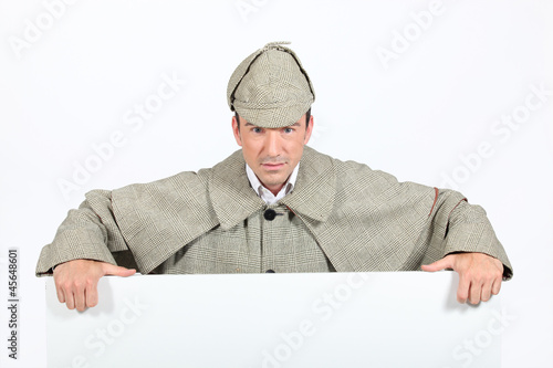 Man in deerstalker and cape leaning on a board