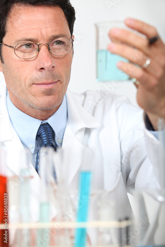 Male scientist holding glass beaker