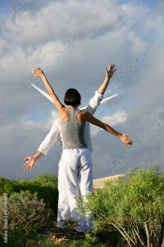 Couple stood mimicking wind farm