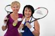two senior women playing tennis