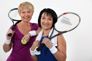 two senior women playing tennis