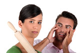 Angry woman threatening man with rolling pin
