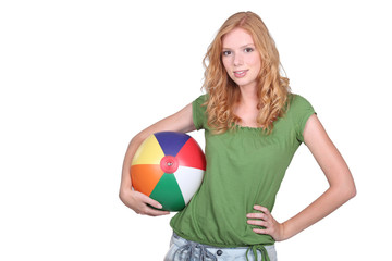 Teenage girl holding beach ball