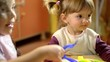 Portrait of happy teacher with children eating in kindergarten