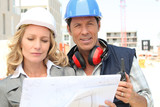 Architect and builder on site with plans