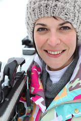 Woman resting skis on shoulder
