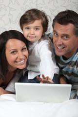 Family laying with laptop