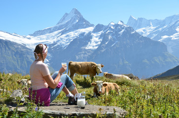 Girl with a jug of milc against herd of cows. Switzerland