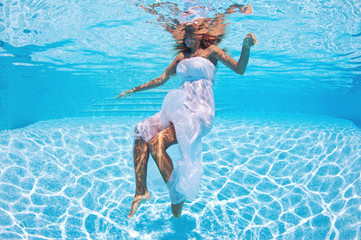 Underwater woman fashion portrait in swimming pool.