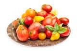Viele Tomaten auf Teller vor weißem Hintergrund
