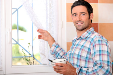 Man with bowl looking out the window