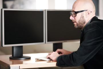 Mann im Büro vor PC Bildschirmen