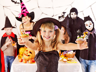 Halloween party with children holding trick or treat.