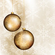 Two golden baubles on bright beige background