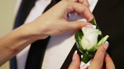 Bride remedies a clothing on a groom