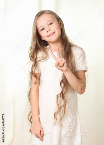 Little beautyful blond girl shows sign victory