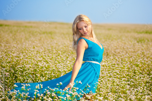 beautiful woman wearing blue dress on a field