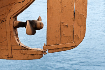 Abstract fragment of old safe-boat propeller and rudder